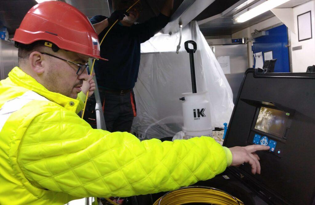 Ibrahim et son collègue nettoient les conduits de l'un des bateaux du client.